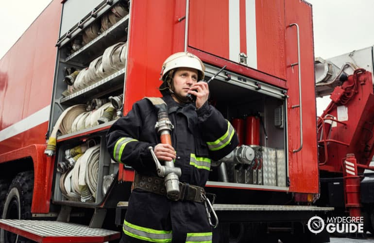 firefighter in action standing near a firetruck