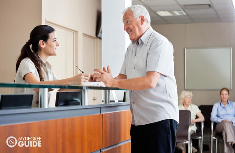 front desk personnel of a nursing home talking to an elderly man