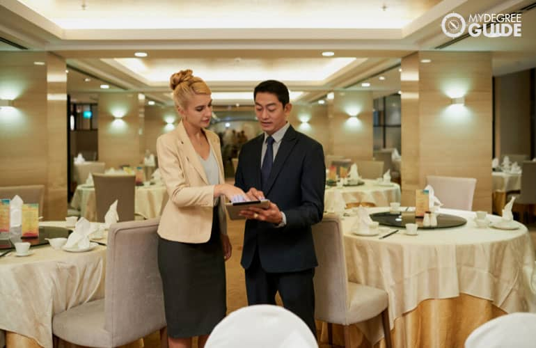 hotel manager talking to an event coordinator in a banquet