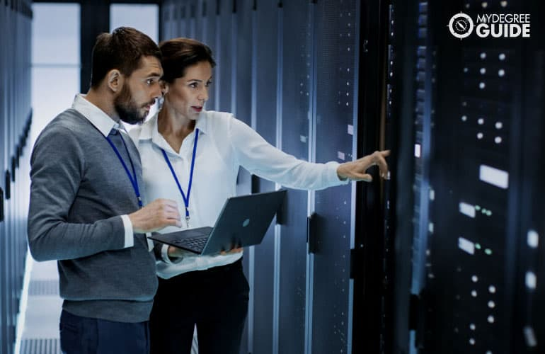 information system administrator with colleague checking their data base