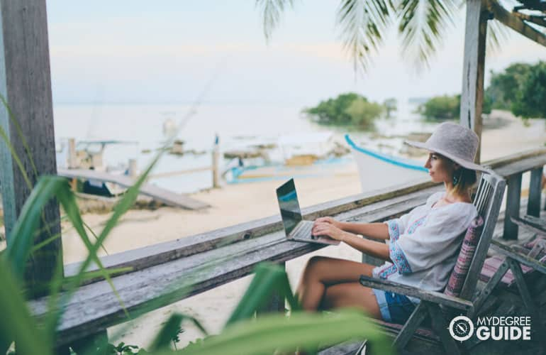 student studying on her computer at a beach