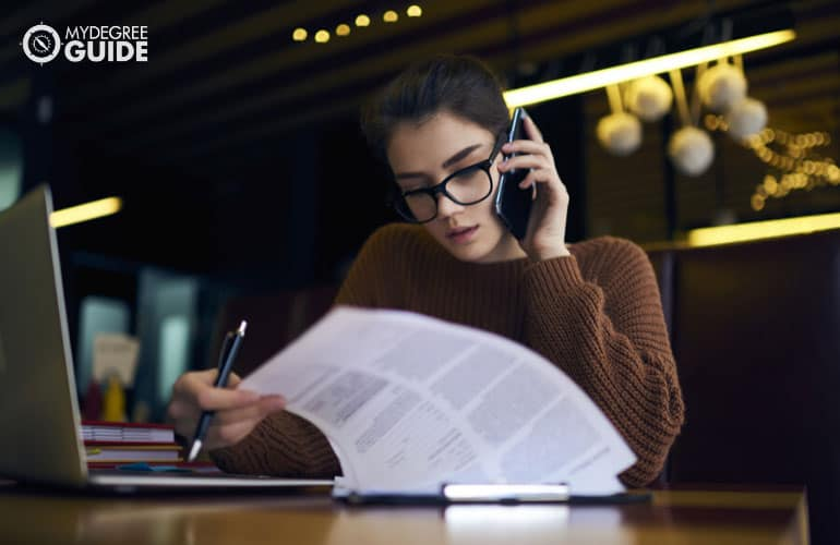 accountant working on documents while talking to a phone