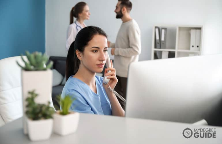 female receptionist talking to phone in a clinic