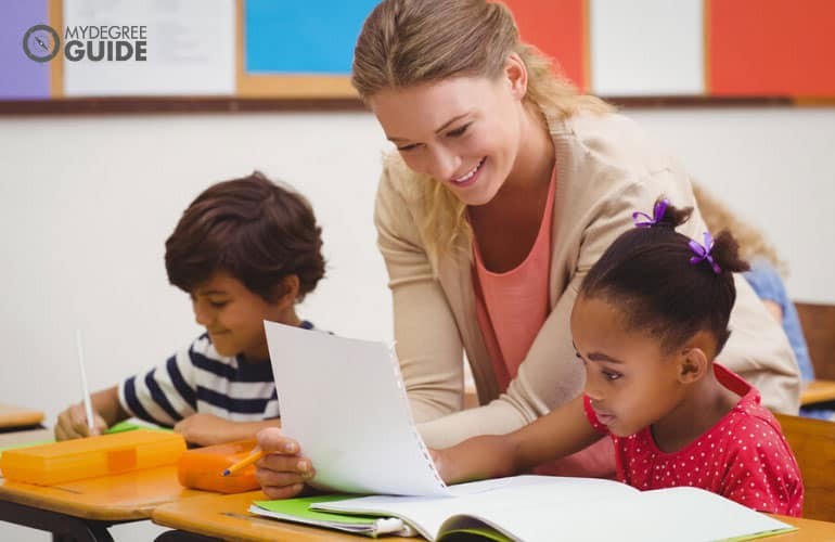 Early Childhood Education teacher teaching young students how to write