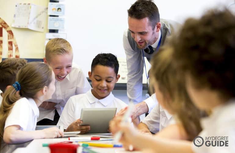 elementary teacher teaching his students using a digital tablet