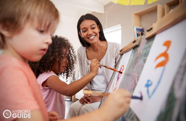 Montessori teacher letting her pupils paint during art session