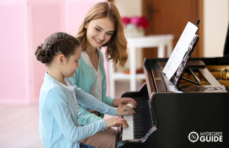 music teacher teaching her student how to play a piano