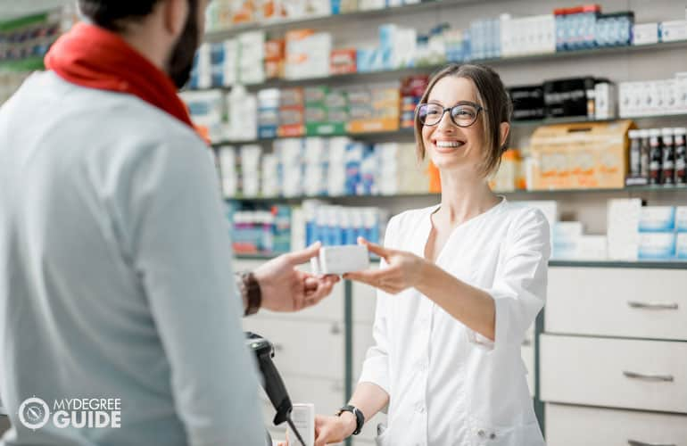 pharmacist giving medicine to a customer