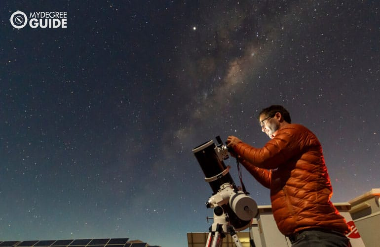 astronomer looking the night sky through an amateur telescope