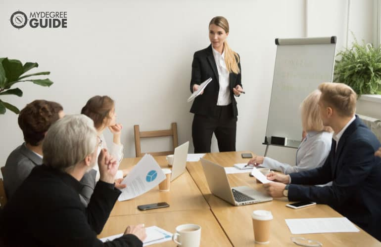 human resources manager training professional employees in a conference room