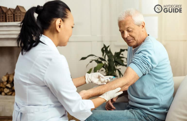 doctor injecting a vaccine to a patient in a senior home