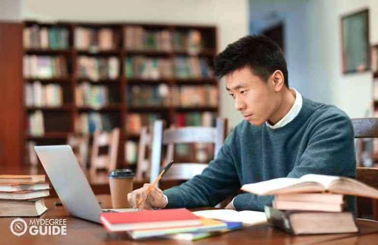 doctorate degree student studying in library with his laptop and books