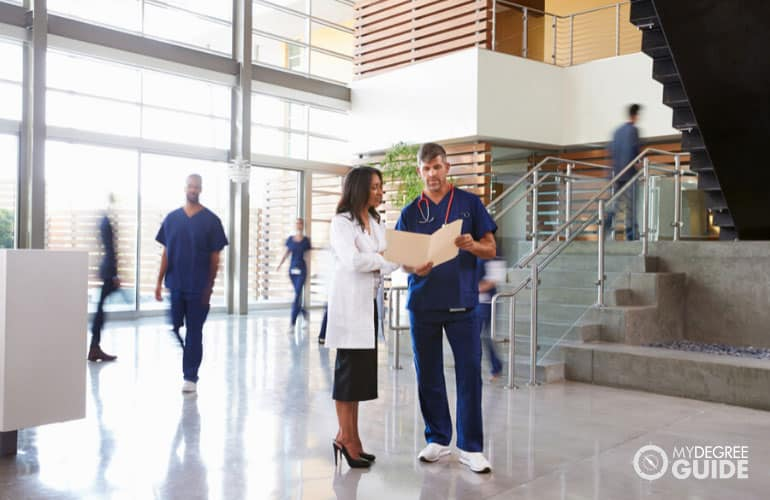 Healthcare Manager talking to a doctor on duty