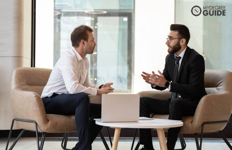 Human Resources Manager having a conversation with a colleague in company lobby