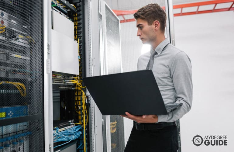 network systems administrator working in data center with his laptop