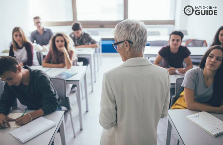 finance professor teaching college students in a classroom