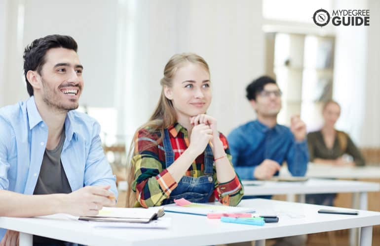 master degree students listening to their professor in university classroom
