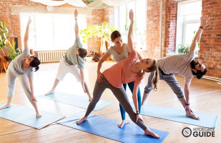 yoga instructor teaching students during yoga session
