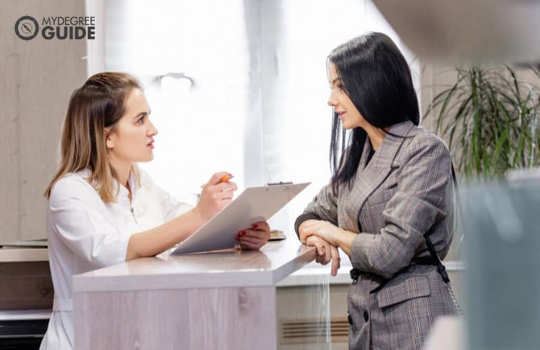 medical receptionist talking to a client