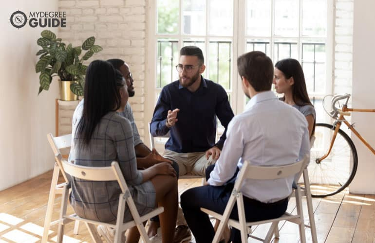 psychologist talking to a group of people during therapy session