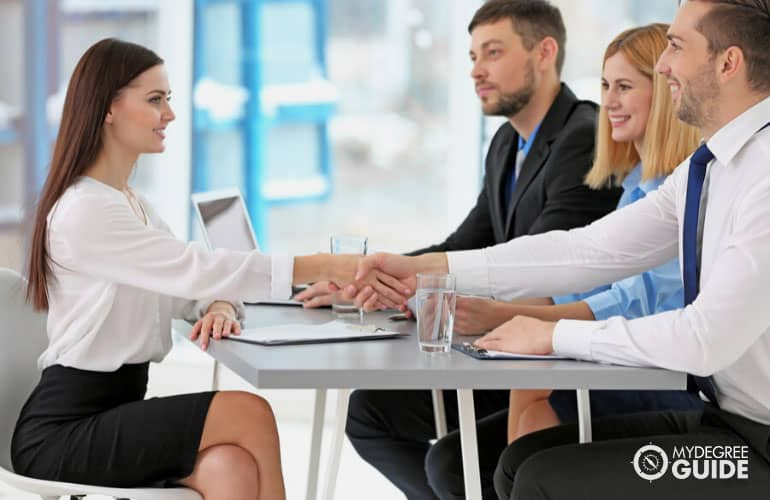 company recruiters shaking hands with potential employee during job interview