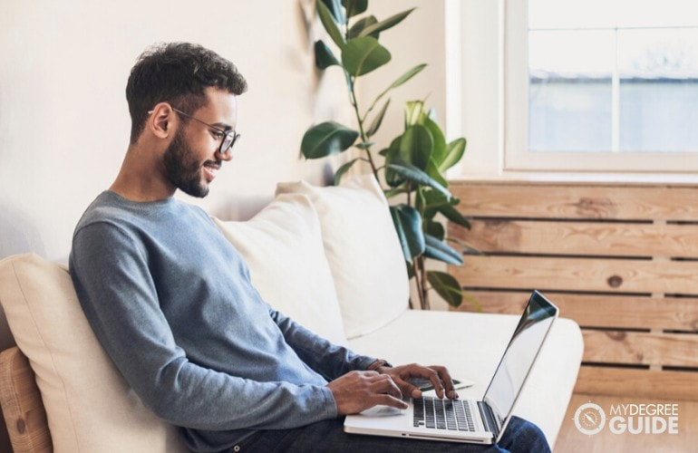 sociology degree student studying on his laptop at home
