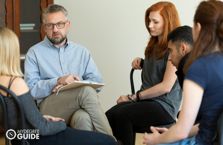 psychiatrist listening to patients during group counseling