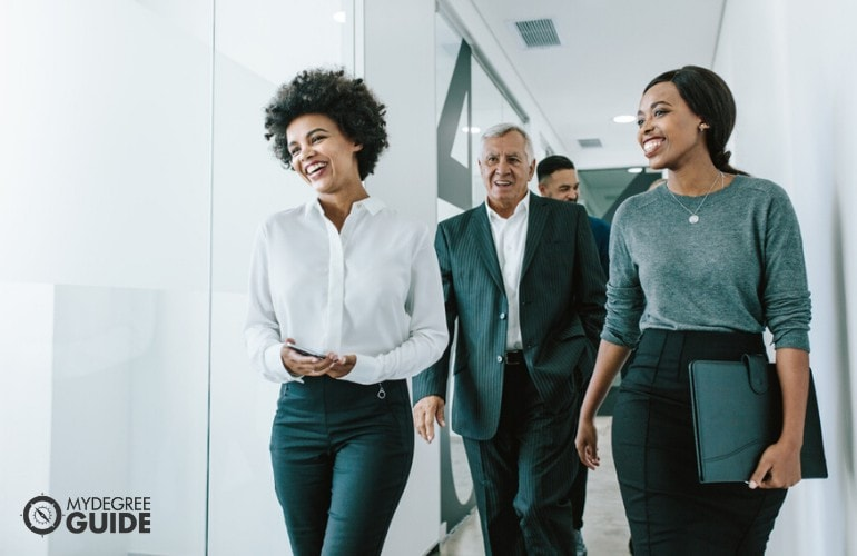 business administrators walking in office aisle