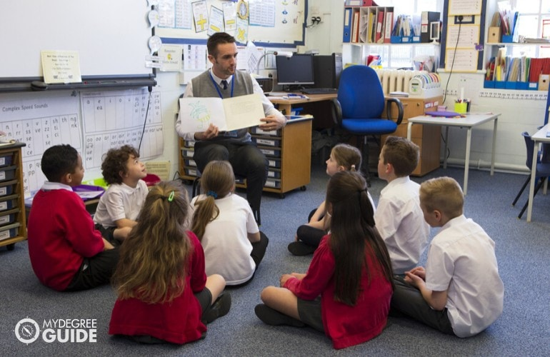 elementary teacher reading a book to his students