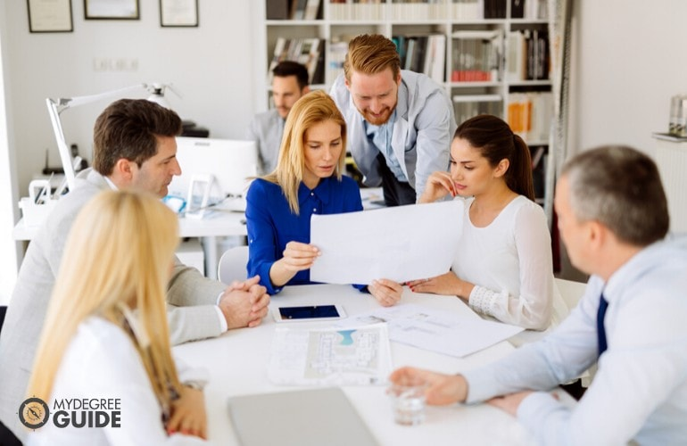 marketing manager checking the work of her team during a meeting