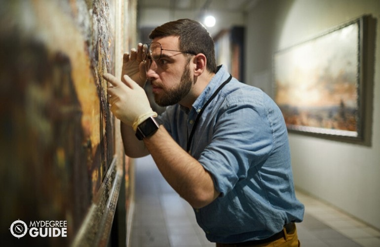 museum curator checking the paintings in a museum