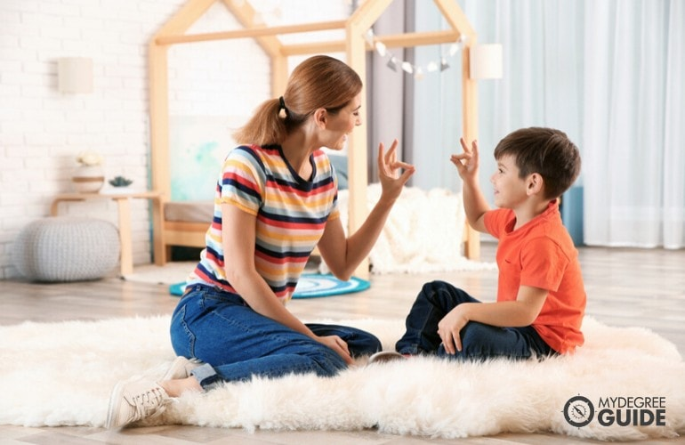 special education teacher having a conversation with a child using sign language
