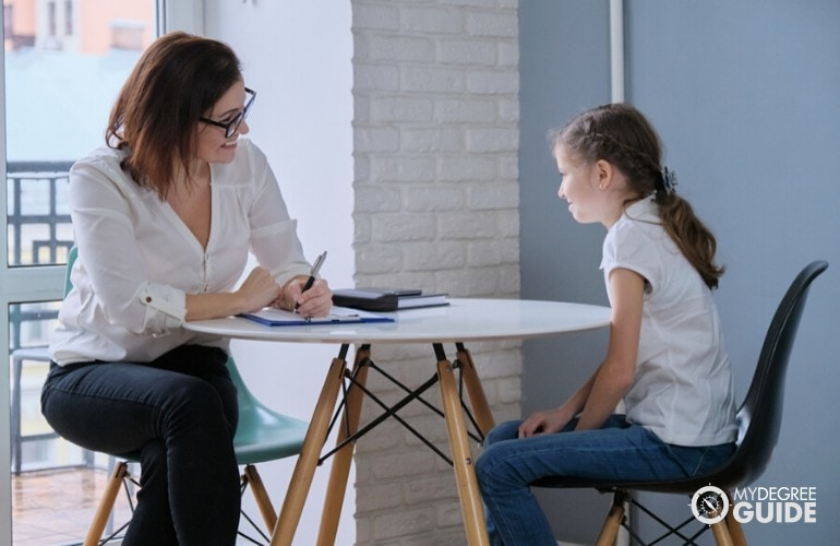 school psychologist talking to a young student