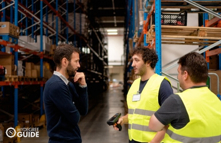 supply chain manager talking to warehouse employees