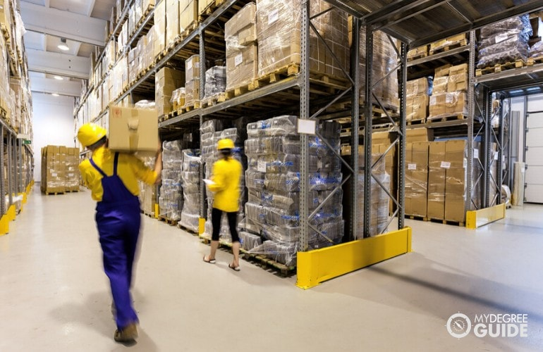 warehouse worker moving a box while being supervised by manager