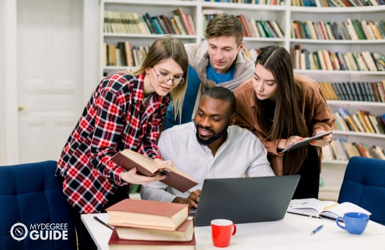 associates of arts students studying together in library