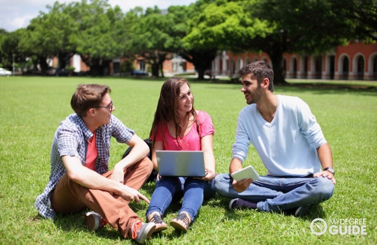 Bachelor's Degree students sitting in university campus grounds