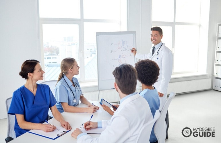 health educator explaining during a meeting with fellow health professionals