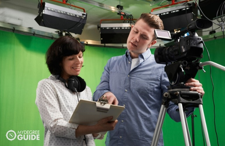 TV producer giving instruction to a camera man