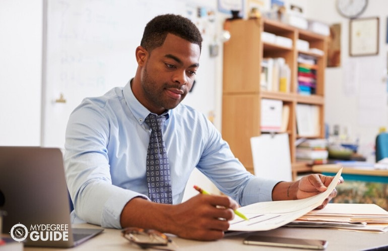 Teacher checking on documents in his office