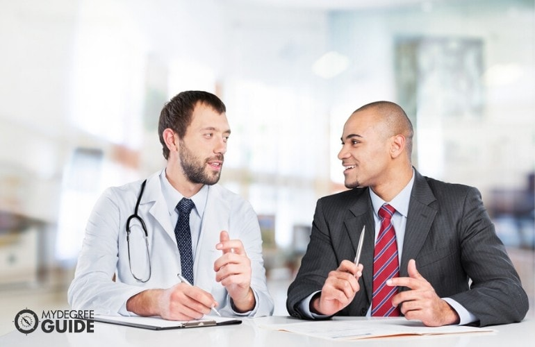 healthcare manager talking to a doctor