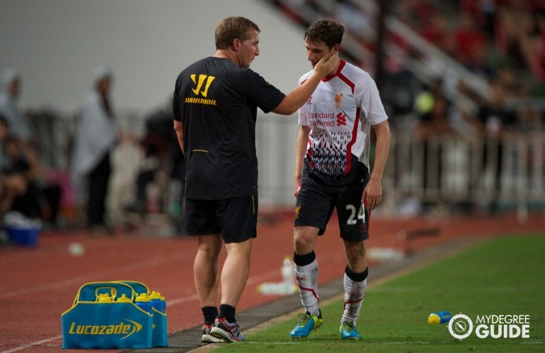 general manager of a soccer team talking to his player