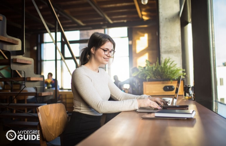Social Media Manager working on her laptop at a cafe