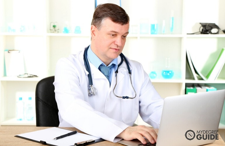 Health Administrator working on his laptop in his office