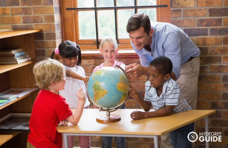 Early Childhood Education teacher teaching his pupils about geography