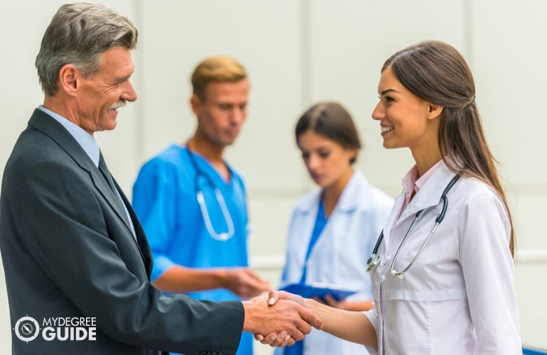 healthcare administrator shaking hands with a doctor