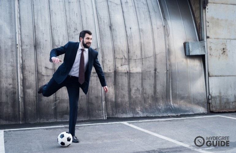 sports manager playing soccer with his team