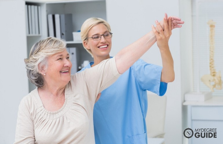nurse helping an elderly woman during therapy