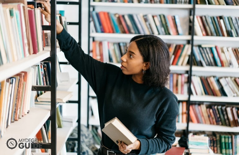 librarian arranging books in a library