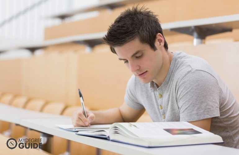 student studying his lessons in lecture hall